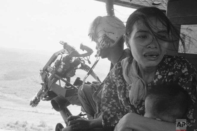 A refugee clutches her baby as a government helicopter gunship carries them away near Tuy Hoa, 235 miles northeast of Saigon on March 22, 1975. They are among thousands fleeing from recent Communist advances. (AP Photo/ Nick Ut)