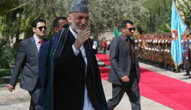 Former Afghan President Hamid Karzai, center, arrives for a ceremony of the peace agreement at the presidential palace in Kabul, Afghanistan, Thursday, Sept. 29, 2016. Afghan President Ashraf Ghani signed a peace treaty with a notorious warlord, pledging to lobby the U.S. and the United Nations to remove him and his party from terrorist blacklists. (AP Photo/Rahmat Gul)