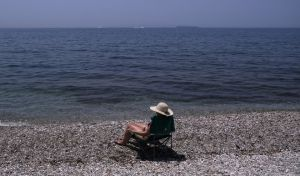 Γυναίκα κάνει ηλιοθεραπεία σε παραλία του Παλαιού Φαλήρου