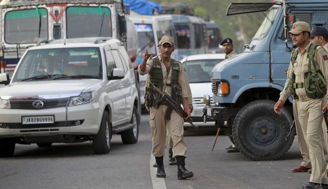 A policeman directs traffic that is halted as part of enhanced security on the Jammu-Srinagar highway in Nagrota outskirts of Jammu, India, Monday, June 13,2016. The security was enhanced after a Central Reserve Police Force (CRPF) camp came under attack on Jammu-Srinagar national highway in Kud area of Udhampur district, of Jammu and Kashmir state. (AP Photo/Channi Anand)