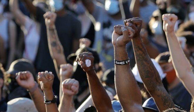 Διαδηλωτές υψώνουν τη γροθιά τους