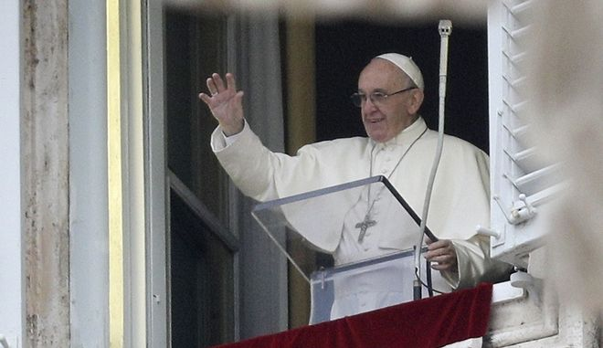 Pope Francis salutes the faithful as he recites the first Angelus prayer of the new year from his studio overlooking St. Peter's square at the Vatican, Monday, Jan. 1, 2018. Francis told people in St. Peter's Square that all must work to secure a future of peace, including for migrants. (AP Photo/Andrew Medichini)