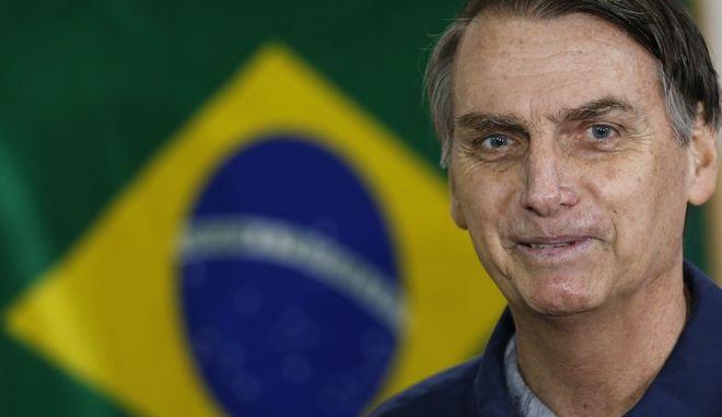 Ο υποψήφιος για τον προεδρικό θώκο της βραζιλίας, Χαΐρ Μπολσονάρου, χαμογελά στους φωτογράφους καθώς προσέρχεται στο εκλογικό κέντρο για να ψηφίσει το μεσημέρι της Κυριακής, 7 Οκτωβρίου.