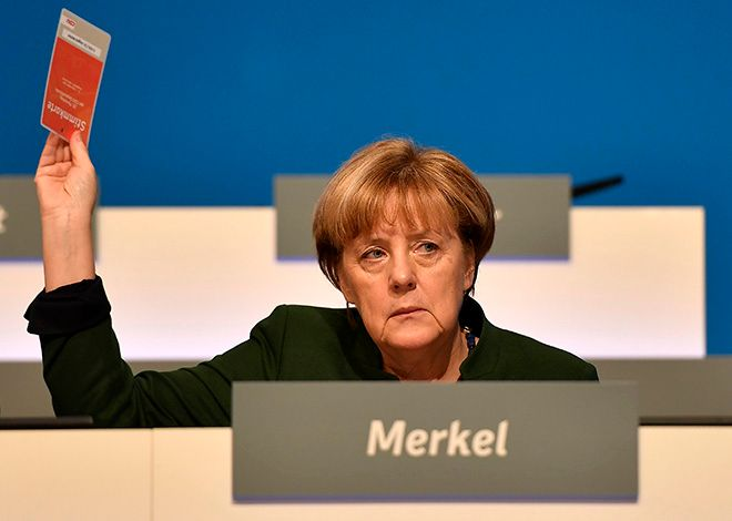 German chancellor Angela Merkel votes at the general party conference of the Christian Democratic Union, CDU, in Essen, Germany, Wednesday, Dec. 7, 2016. Merkel has won a new term as the leader of Germany's main conservative party after stressing her determination to prevent a repeat of last year's huge migrant influx and advocating a partial ban on face-covering veils. (AP Photo/Martin Meissner)
