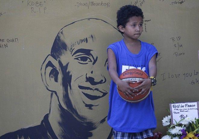 Ένα μικρό αγόρι μπροστά από γκραφίτι για τον Kobe Bryant