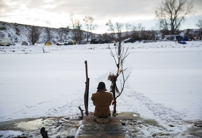 Army veteran Nick Biernacki, of Indiana, prays at the Cannonball River at the Oceti Sakowin camp where people have gathered to protest the Dakota Access oil pipeline in Cannon Ball, N.D., Sunday, Dec. 4, 2016. Tribal elders have asked the military veterans joining the large Dakota Access pipeline protest encampment not to have confrontations with law enforcement officials, an organizer with Veterans Stand for Standing Rock said Sunday, adding the group is there to help out those who've dug in against the four-state, $3.8 billion project. (AP Photo/David Goldman)