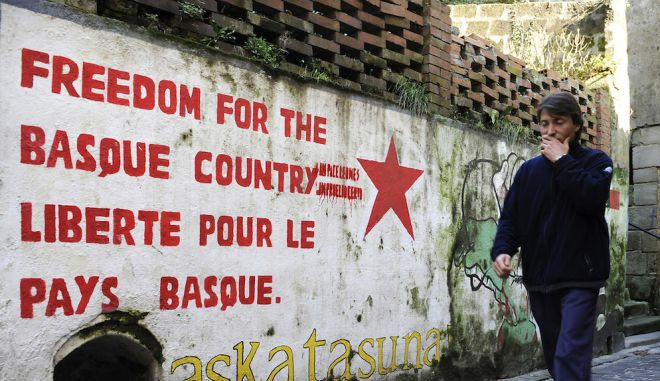 an unidentified man walks past a pro independence mural painting in the northern Spanish Basque village of Pasajes de San Pedro, on February 18, 2009. AFP PHOTO/Rafa Rivas