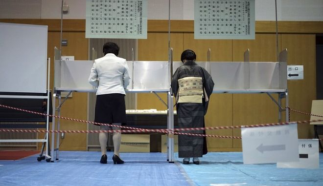 Voter fills in their ballots in a general election at a polling station in Tokyo Sunday, Oct. 22, 2017. Voting has kicked off for Japans general election on Sunday that would most likely hand Prime Minister Shinzo Abes ruling coalition a win, possibly retaining two-thirds in the parliament. (AP Photo/Eugene Hoshiko)