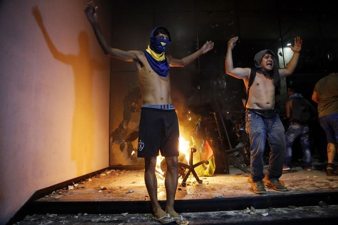 People chant slogans outside the Congress building during clashes between police and protesters opposing an approved proposed constitutional amendment that would allow the election of a president to a second term,  in Asuncion, Paraguay, Friday, March 31, 2017. Some protesters broke through police lines and entered the first floor, where they set fire to papers and furniture. Police used water cannon and fired rubber bullets to drive demonstrators away from the building while firefighters extinguished blazes inside. (AP Photo/Jorge Saenz)