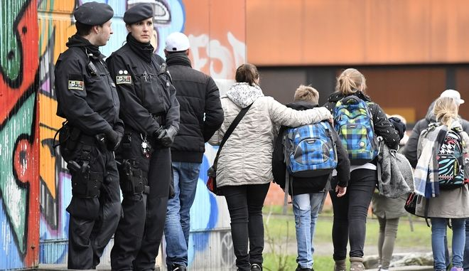 Parents take their children home from the Kaethe-Kollwitz school in Luenen, Germany, Tuesday, Jan. 23, 2018. Police say a student has been killed by a fellow pupil at a school in western Germany. Dortmund police said the incident happened Tuesday morning at a school in the nearby town of Luenen.  Police said a minor has been arrested and investigations into the killing are ongoing. Students and teachers at the school are getting psychological counseling. (AP Photo/Martin Meissner)