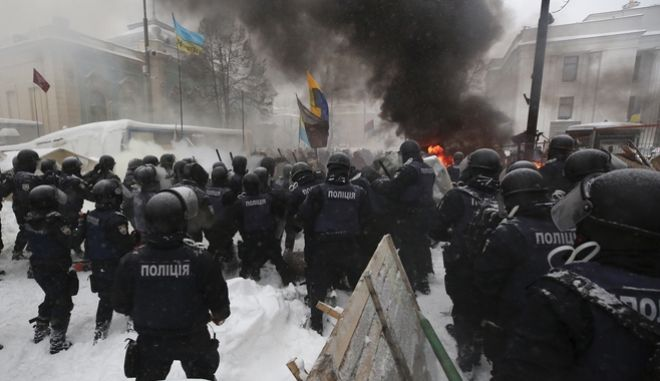 Riot police destroy a tent camp installed by activists of the Movement of New Forces, the political party led by Mikheil Saakashvili, as protesters fire tires in Kiev, Ukraine early Saturday, March 3, 2018. Protesters demand President Petro Poroshenko's impeachment. (AP Photo/Serhii Nuzhnenko)