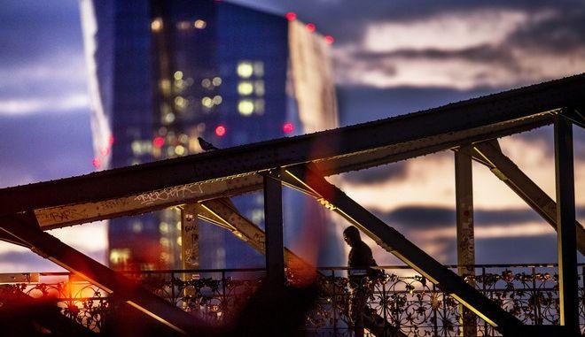 Άνδρας περπατάει σε μια γέφυρα με φόντο την Ευρωπαική Κεντρική Τράπεζα