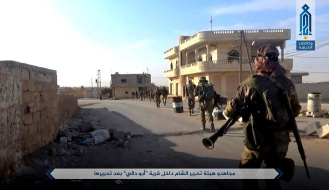 "This photo released on Sunday, Oct 8, 2017 by the al-Qaida-affiliated Ibaa News Agency, that is consistent with independent AP reporting, purports to show al-Qaida-linked fighters from Hayat Tahrir al-Sham or Levant Liberation Committee walk inside the Syrian village of Abu Dali in Idlib province, after they captured from Syrian troops. The fight in Abu Dali comes amid reports of an imminent Turkish-backed operation in the northwestern Idlib province against the militants. Arabic reads, ""Jihadists from Hayat Tahrir al-Sham inside Abu Dali village after liberating it."" (Ibaa News Agency, via AP)"