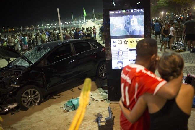People watch the site of the accident where a car that has driven into the crowded seaside boardwalk along Copacabana beach in Rio de Janeiro, Brazil, Thursday, Jan. 18, 2018. Military police said on Twitter that at least 11 people were injured and that the driver has been taken into custody. (AP Photo/Silvia Izquierdo)