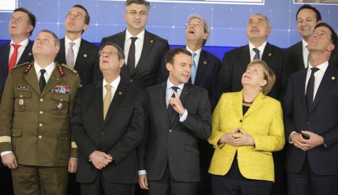 French President Emmanuel Macron, front center, speaks with German Chancellor Angela Merkel, front second right, as they look up at a drone flying above their heads during a group photo at an EU summit at the Europa building in Brussels on Thursday, Dec. 14, 2017. European Union leaders are gathering in Brussels and are set to move Brexit talks into a new phase as pressure mounts on Prime Minister Theresa May over her plans to take Britain out of the 28-nation bloc. (AP Photo/Olivier Matthys)