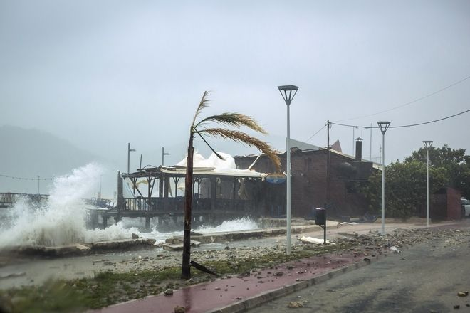 Waves break on a seaside tavern during a storm at the port of Argostoli, on the Ionian island of Kefalonia, western Greece, Friday, Sept. 18, 2020. A powerful tropical-like storm named Ianos battered the western islands of Zakynthos, Kefalonia, and Ithaki overnight, causing flash flooding, property damage, power outages, and road closures mostly from downed trees, police and local authorities said. (AP Photo/Nikiforos Stamenis)