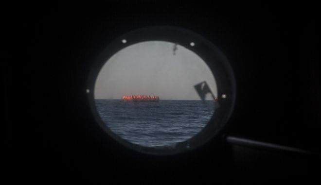 Refugees and migrants from different African countries aboard an overcrowded rubber boat are seen trhought a hatch from Golfo Azzurro, the Spanish NGO Proactiva Open Arms rescue ship, about 20 miles North of Sabratha, Libya, Saturday, March 4, 2017. A rescue ship belonging to a Spanish NGO has saved 250 migrants in danger of capsizing near the Libyan coast on Saturday. Proactiva Open Arms spokesperson Laura Lanuza says that the NGO's boat rescued the African migrants from two small rubber vessels that were at risk of being overwhelmed by the sea. (AP Photo/Santi Palacios)