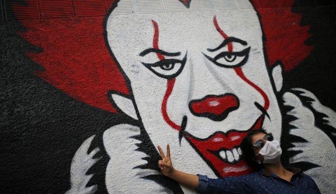 Γυναίκα με μάσκα για τον κορονοϊό ποζάρει μπροστά από γκράφιτι