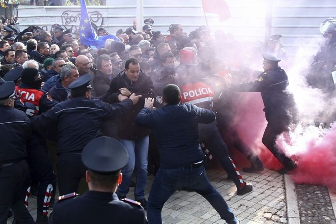 Demonstrators scuffle with riot police during a protest against a vote to appoint a temporary prosecutor general, which they consider to be unconstitutional in Tirana, Monday, Dec. 18, 2017. Albanian police have clashed with opposition supporters trying to force their way into and disrupt a session of parliament. (AP Photo)