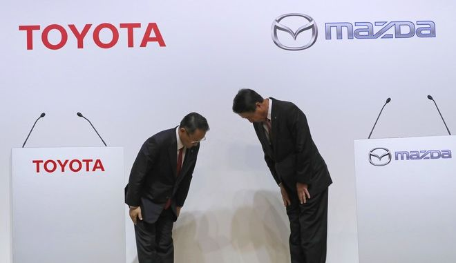 Toyota Motor Corp. President Akio Toyoda, left, and Mazda Motor Corp. President Masamichi Kogai, right, bow to each other prior to a press conference in Tokyo Friday, Aug. 4, 2017.  Japanese automakers Toyota Motor Corp. and Mazda Motor Corp. said Friday they plan to spend $1.6 billion to set up a joint-venture auto manufacturing plant in the U.S.  a move that will create up to 4,000 jobs. (AP Photo/Eugene Hoshiko)