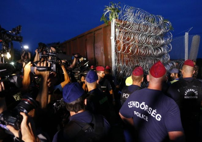 Hungarian police officers guard the area as a rail wagon prepared with barbwire arrives to seal the border fence between Serbia and Hungary in Roszke, southern Hungary, Monday, Sept. 14, 2015. Hungary are set to introduce much harsher border controls at midnight  laws that would send smugglers to prison and deport migrants who cut under Hungary's new razor-wire border fence. The country's leader was emphatically clear that they were designed to keep the migrants out. (AP Photo/Matthias Schrader)