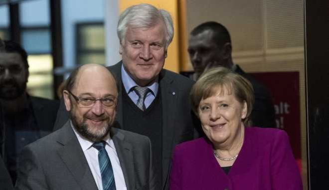 Martin Schulz, chairman of the German Social Democratic Party (SPD), front left, German Chancellor and chairwomen of the German Christian Democratic Union Party (CDU), Angela Merkel, front right, and Horst Seehofer, rear center, chairman of the Christian Social Union Party  (CSU), arrive for coalition negotiations on a new German government between the Christian Unions bloc and the Social Democratic Party (SPD) in Berlin, Germany, Friday, Feb. 2, 2018. (Bernd von Jutrczenka/dpa via AP)