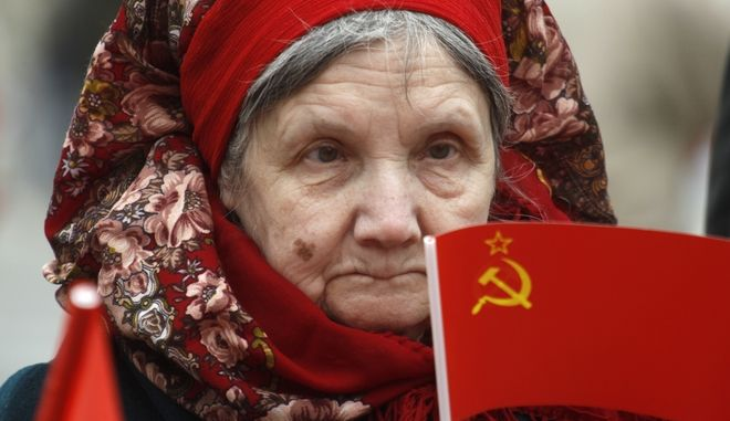 An elderly Russian woman carries Soviet flag during a communist Party supporters rally to mark May Day in Moscow, Russia, Tuesday, May 1, 2012. (AP Photo/Mikhail Metzel)