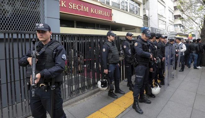 Riot police stand guard as people queue in front of Turkey's Supreme Electoral Board in Ankara, Turkey, Tuesday, April 18, 2017. Turkey's prime minister on Tuesday called on the opposition to respect the result of a referendum that will give sweeping new powers to the office of the president, but the main opposition party formally requested the vote be annulled. (AP Photo/Burhan Ozbilici)