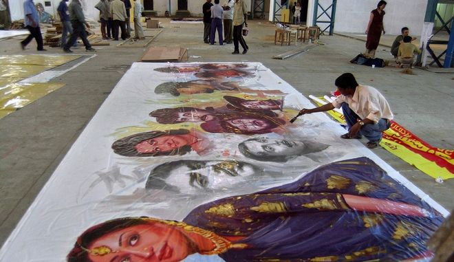 An artist paints the portraits of famous Bollywood actors on the eve of the World Social Forum (WSF) conference in Bombay, India, Thursday, Jan. 15, 2004. Thousands of anti-globalization activists are gathering in Bombay for the WSF between Jan.16 and 21. (AP Photo/Rajesh Nirgude)