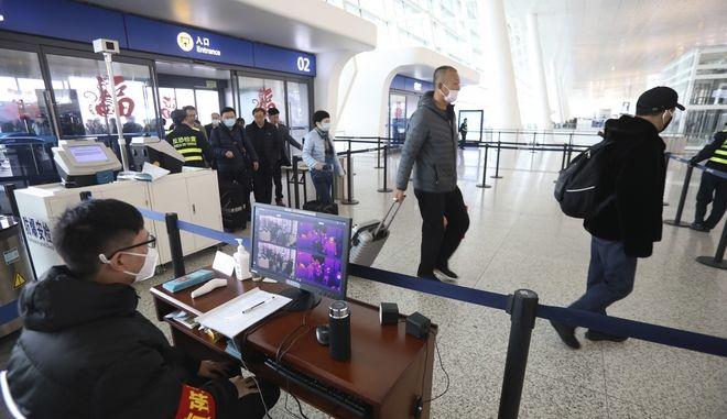 """Υπάλληλος """"ελέγχει"""" τους επιβάτες σε αεροδρόμιο της Κίνας για πιθανά κρούσματα του ιού."""