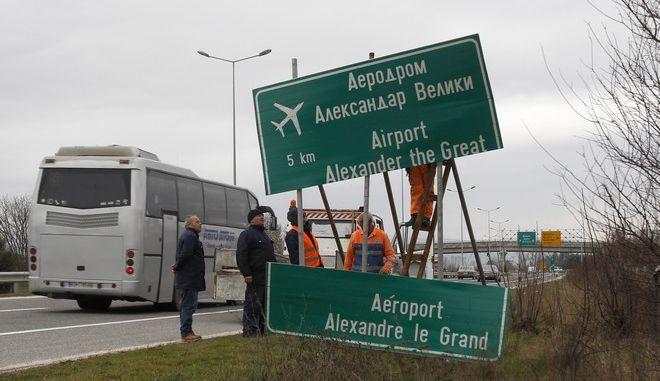 Εργάτες ξηλώνουν σημάνση προς το αεροδρόμιο των Σκοπίων (Φωτογραφία αρχείου)