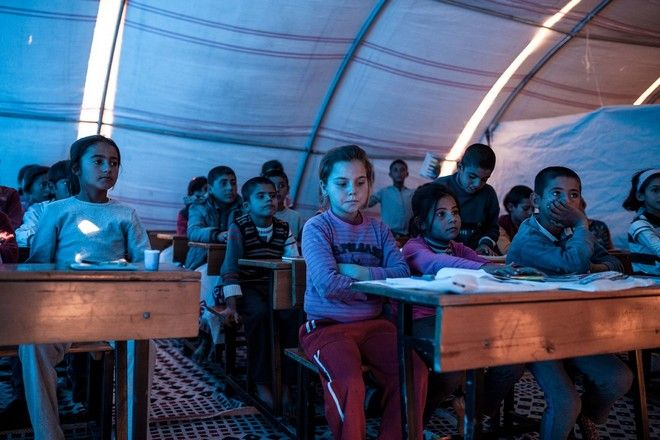 Kurdish children from Kobani take lesson in an improvised classroom in 'Kobani' refugee camp in the border town of Suruc, Sanliurfa province, Turkey on November 10, 2014.