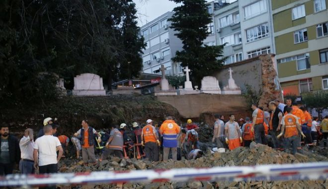 Firefighters work at the scene after part of stone wall surrounding an Armenian cemetery was demolished in a storm, in Istanbul, Thursday, July 27, 2017. At least three people were reported injured on Thursday after a severe summer storm hit Istanbul, knocking down a wall and trees and flooding the Turkish citys streets and underpasses. (AP Photo/Emrah Gurel)
