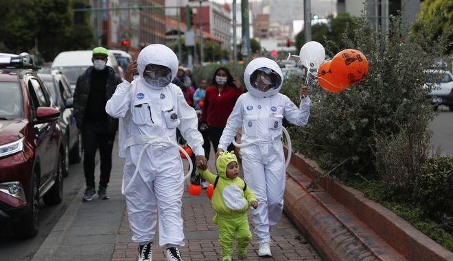 Άνθρωποι φορούν στολή αστροναύτη για να προστατευθούν από τον κορονοϊό