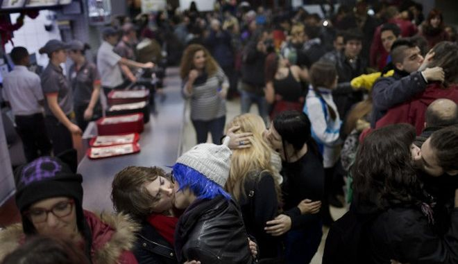 Same sex couples kiss inside a Burger King restaurant in Madrid, Spain, Saturday, Dec. 6, 2014 . People supporting the fight against homophobia gathered on Saturday in a restaurant to protest against the decision of a security guard that asked a gay couple to leave the place after they kissed. (AP Photo/Daniel Ochoa de Olza)