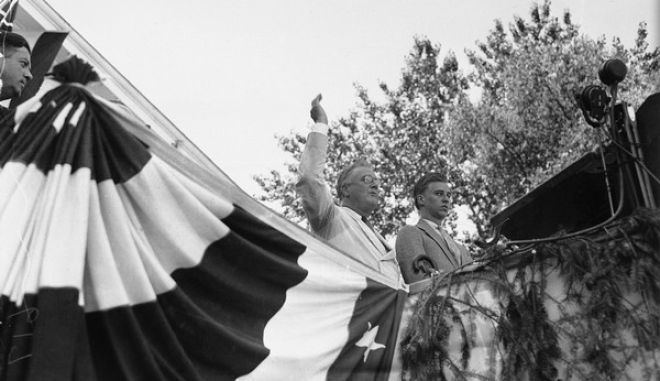 President Franklin Roosevelt waves to the crowds in Green Bay, Wis. Aug. 9, 1934. President Roosevelt defended the New Deal in his last cross-country speech before returning to Washington, D.C. At right is his son John Roosevelt, who accompanied him on his vacation cruise. (AP Photo)