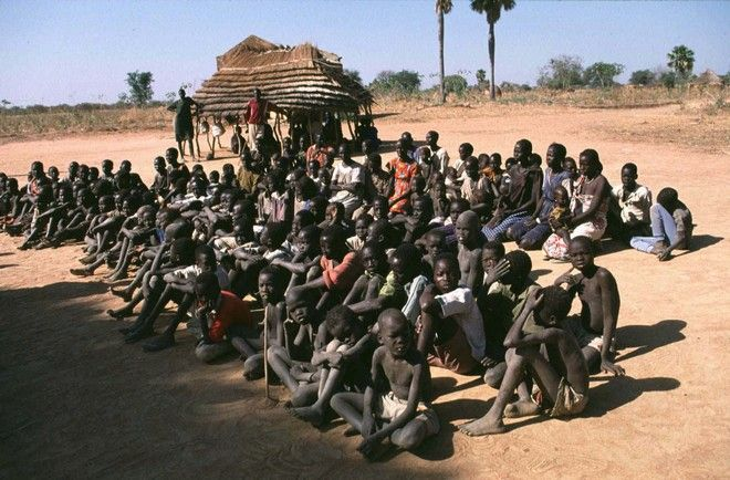 Women and children, former slaves wait to be released in Madhol, southwest of Khartoum, Dec. 13, 1997. An Arab trader sold the people for $13,200 in Sudanese money to the Christian Solidarity International. The Swiss-based charity, which estimates tens of thousands of black slaves are owned by Arabs in northern Sudan, has redeemed 800 since 1995.  (AP Photo/Jean-Marc Bouju)
