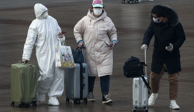 Ταξιδιώτες με αποσκευές φορώντας μάσκες για προστασία από τον κοροναϊό