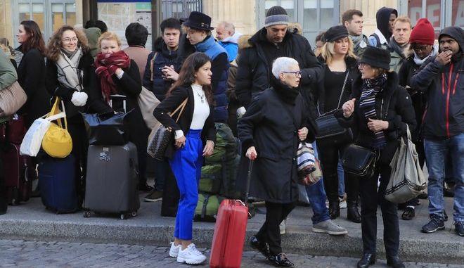 Τουρίστες αναμένουν λεωφορείο έξω από σταθμό τρένων