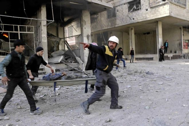 This photo released Tuesday Feb. 20, 2018, provided by the Syrian Civil Defense group known as the White Helmets, shows members of the Syrian Civil Defense group carrying a man who was wounded  during airstrikes and shelling by Syrian government forces, in Ghouta, a suburb of Damascus, Syria. Intense Syrian government shelling and airstrikes of rebel-held Damascus suburbs killed at least 100 people since Monday in what was the deadliest day in the area in three years, a monitoring group and paramedics said Tuesday. (Syrian Civil Defense White Helmets, via AP)