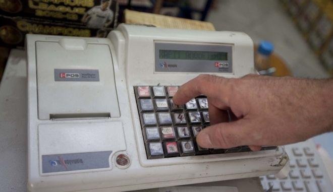 Πελάτης παραλαμβάνει την απόδειξη σε κατάστημα της Λάρισας την Παρασκευή 12 Ιουλίου 2013. Το σχέδιο του υπουργού Οικονομικών Γιάννη Στουρνάρα προβλέπει το Σεπτέμβριο στη Βουλή ένα νέο νόμο με όλα τα φορολογικά κίνητρα που θα προσφέρει το κράτος σε καταναλωτές και επενδυτές, προκειμένου να τους έχει συμμάχους στην μάχη της καταπολέμησης των ελλειμμάτων και της ύφεσης.  Το σχέδιο προανήγγειλε ο ίδιος ο υπουργός Οικονομικών μιλώντας στη Βουλή και θα αφορά τα εισοδήματα και τις δαπάνες  από 1/1/2013. (EUROKINISSI/ΚΩΣΤΑΣ ΜΑΝΤΖΙΑΡΗΣ)