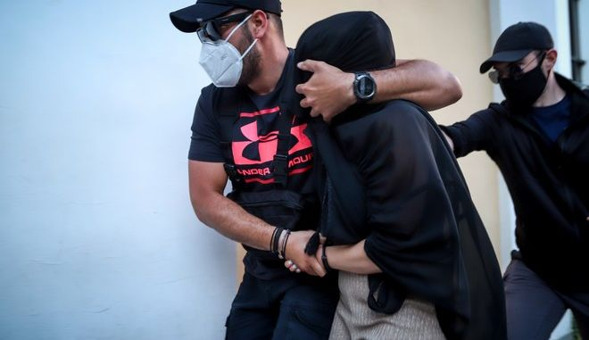 Η 36χρονη η οποία κατηγορείται για την επίθεση με βιτριόλι οδηγείται από αστυνομικούς στον ανακριτή.