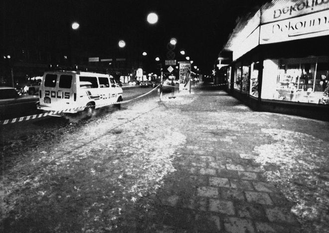 A police van is standing close to the spot where Swedish Prime Minister Olof Palme was assassinated at the crossing Tunnelgatan-Sveavaagen in Stockholm City on Friday, March 1, 1986. The dark spot in the snowless middle of the pavement is blood from the Prime Minister. That is where he was shot by a gun-man in close range. (AP Photo/Bjorn Elgstrand)