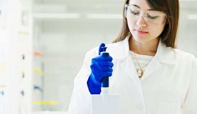 Scientist using multichannel pipetter in lab