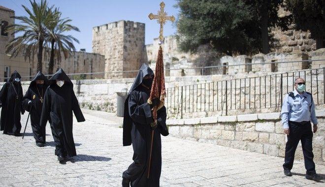 Κληρικοί με μάσκες και γάντια προχωρούν προς τον Πανάγιο Τάφο