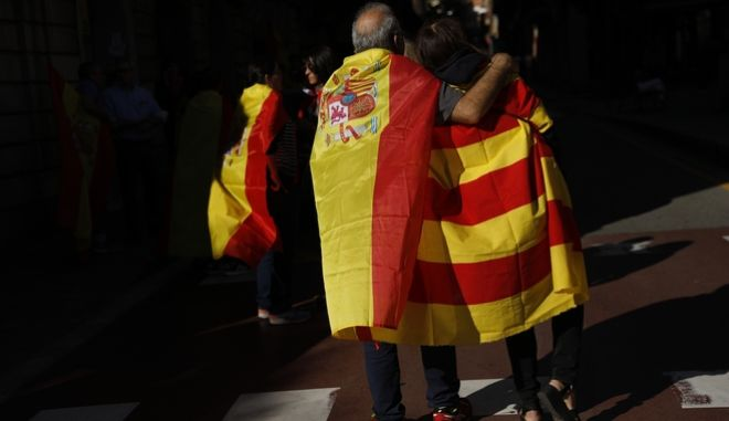 A man draped in a Spanish flag walks with a woman draped in a Catalan flag on their way to during a mass rally against Catalonia's declaration of independence, inBarcelona, Spain, Sunday, Oct. 29, 2017. Thousands of opponents of independence for Catalonia held the rally on one of the city's main avenues after one of the country's most tumultuous days in decades.(AP Photo/Gonzalo Arroyo)