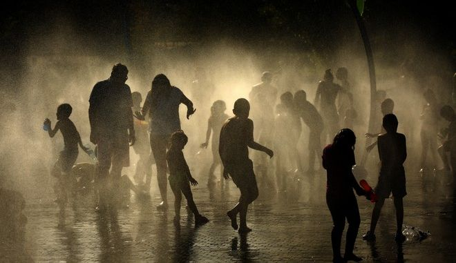People cool off in an urban beach at Madrid Rio park in Madrid, Wednesday, June. 26, 2019. Hot air from Africa is bringing a heat wave to Europe, prompting health warnings about Sahara Desert dust and exceptionally high temperatures in Spain. (AP Photo/Manu Fernandez)