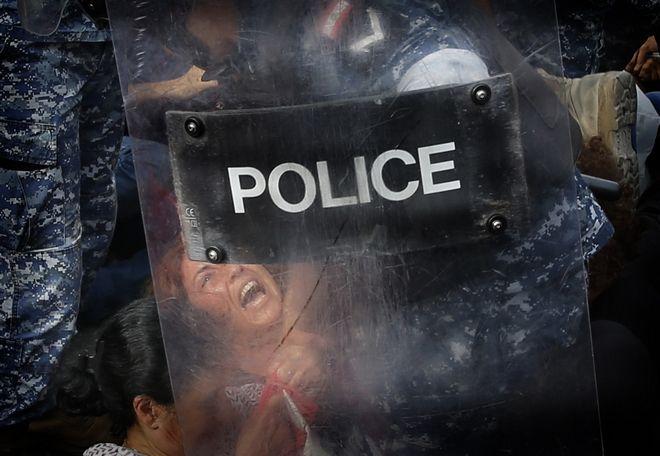 Ένας αστυνομικός απομακρύνει αντικυβερνητική διαδηλώτρια