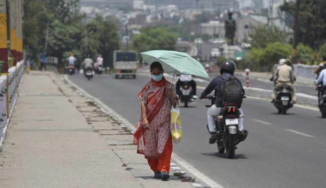 Γυναίκα στην Ινδία φοράει μάσκα για τον κορονοϊό