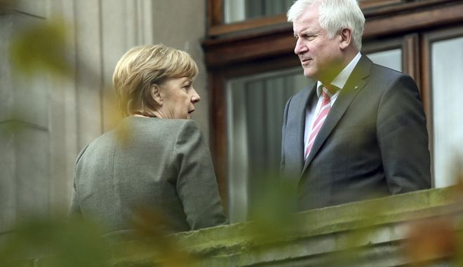 Chancellor Angela Merkel, left, talks to Bavarian governor Horst Seehofer during talks on forming a new government in Berlin Thursday, Oct. 26 2017. (Maurizio Gambarini/dpa via AP)